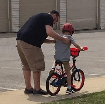 Kyle teaching Ethan to ride a bike