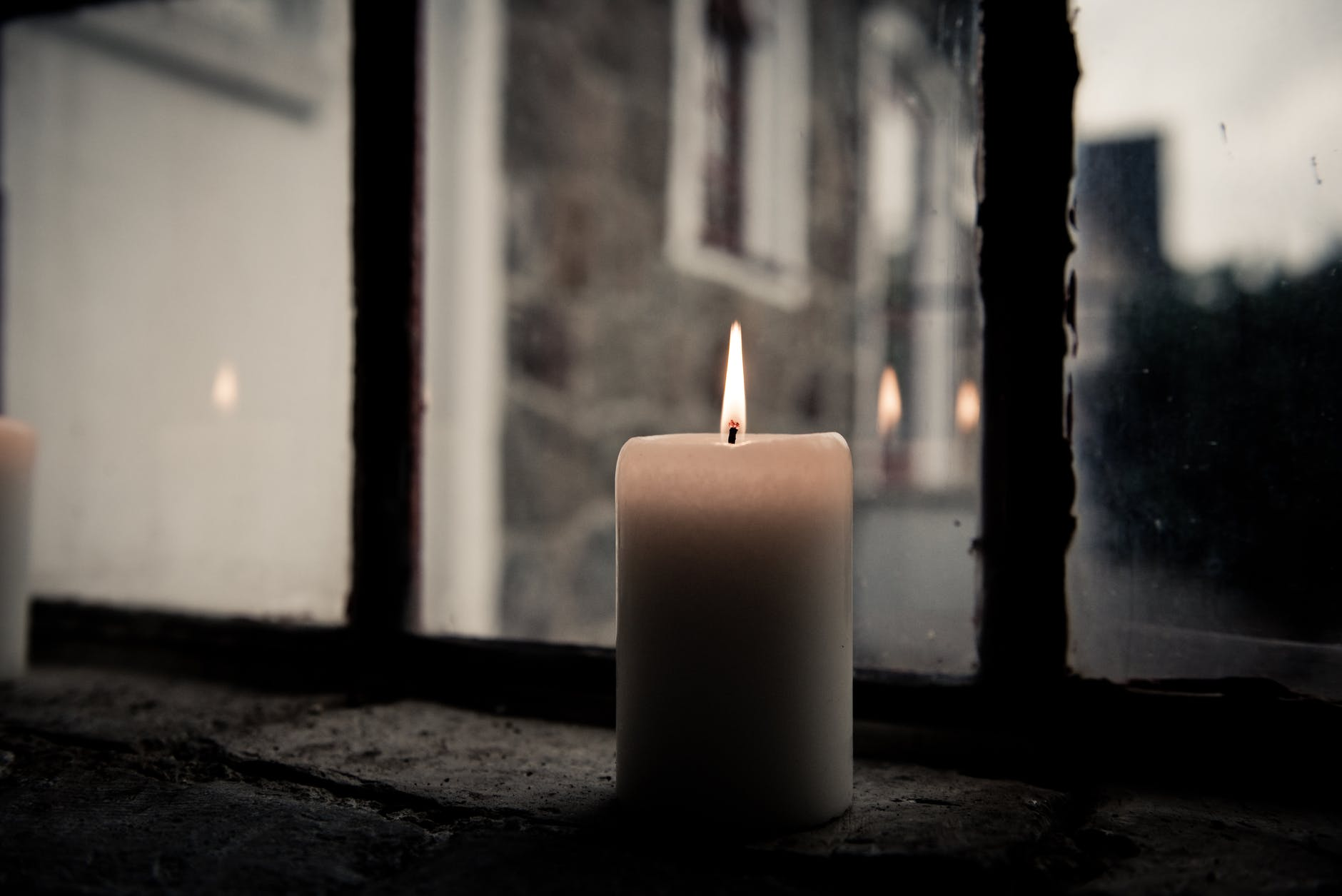 pillar candle near clear glass window