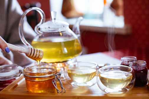 teapot and teacups with tea and honey on tray
