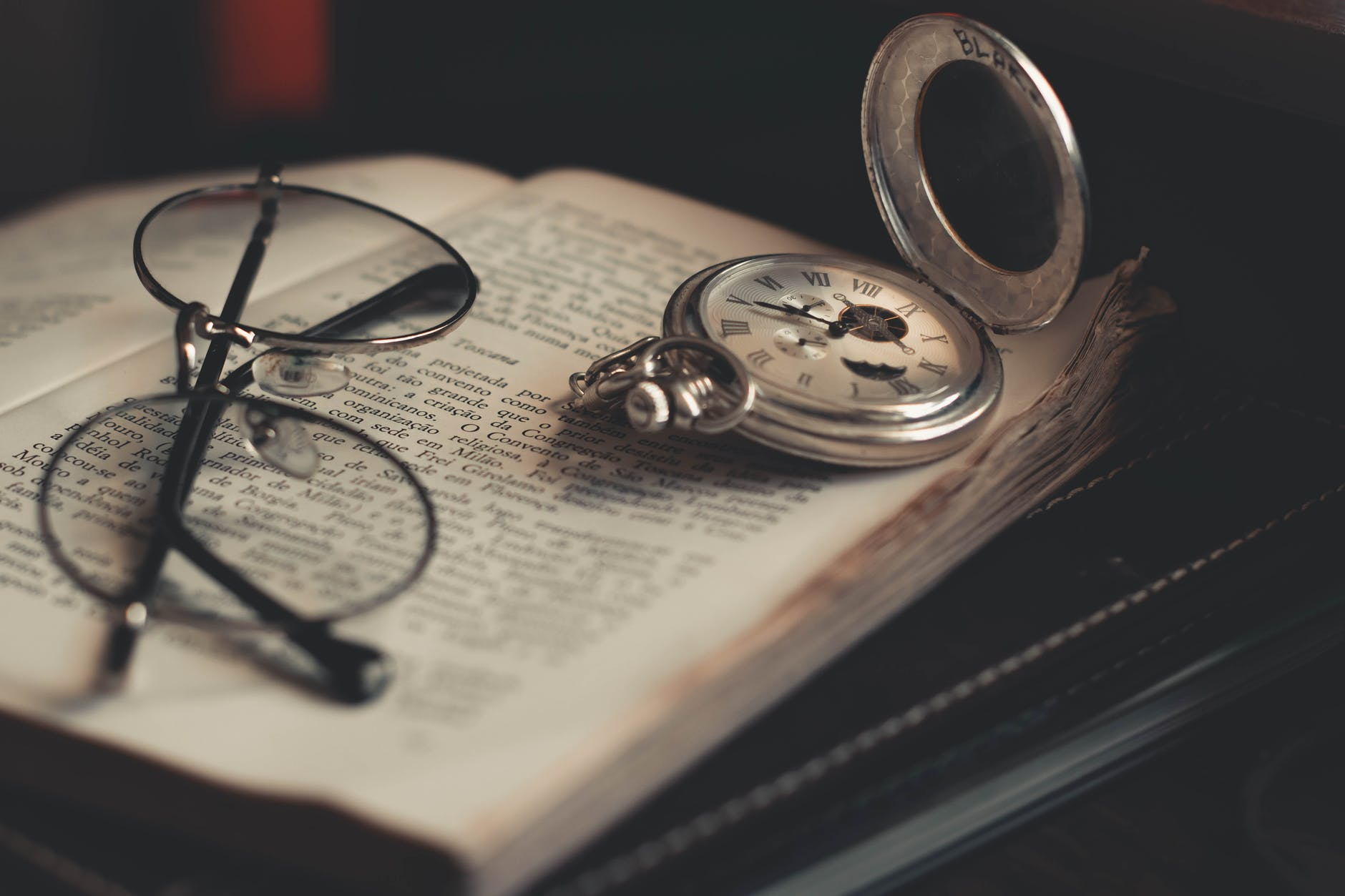 round silver colored pocket watch and eyeglasses on opened book